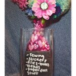 A pink flower vase with hearts in a square flower vase. Inside the square vase is a slate coaster with a to-do list written on it. The heart vase has fake flowers and pompoms as flowers.